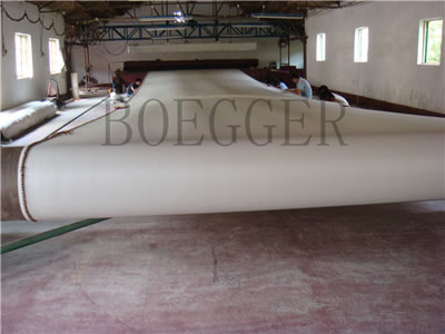 A large loom is producing the white polyester filter belt.